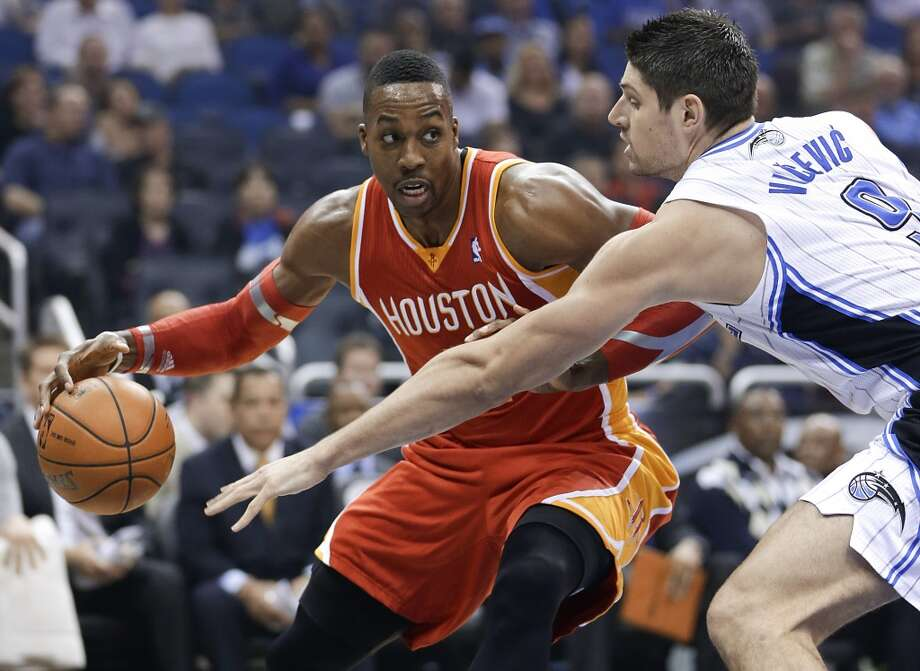 Dwight Howard, left, makes a move to get around Nikola Vucevic. Photo: John Raoux, Associated Press