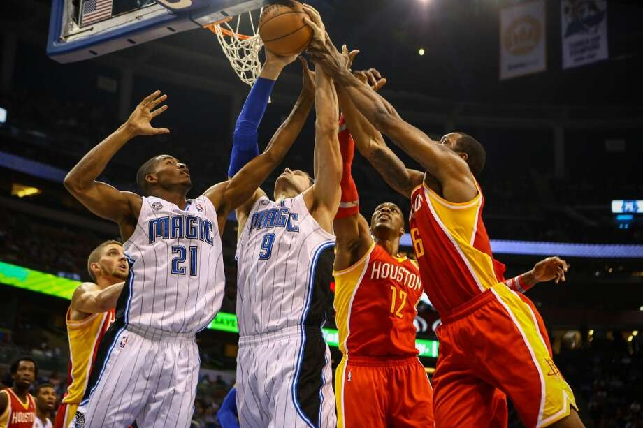 Nikola Vucevic (9) grabs the rebound ahead of the Terrence Jones (6) and Dwight Howard (12). Photo: Joshua C. Cruey, McClatchy-Tribune News Service