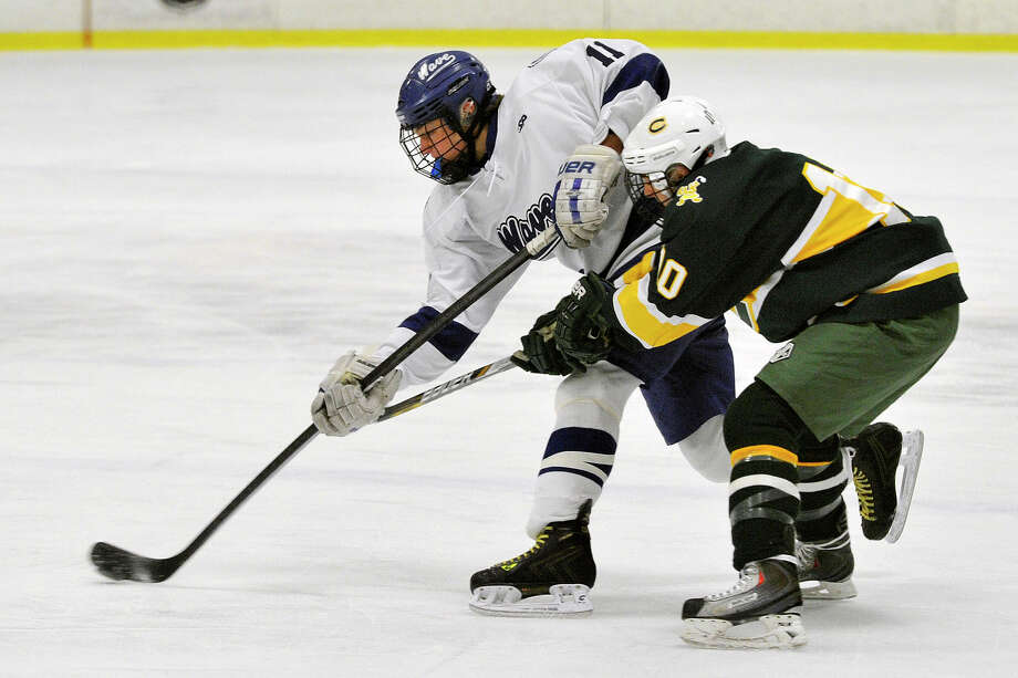 Darien's Nicholas Tuzinkiewicz passes the puck while under pressure from Trinity Catholic's Griffin Northrop during their FCIAC semifinal hockey game at Terry Conners Rink in Stamford, Conn., on Wednesday, March 5, 2014. Photo: Jason Rearick / Stamford Advocate