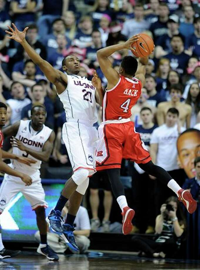 Connecticut's Lasan Kromah  (20) guards Rutgers' Myles Mack (4) during the second half of  Connecticut's 69-63 victory in an NCAA college basketball game in  Storrs, Conn., Wednesday, March 5, 2014. (AP Photo/Fred Beckham)