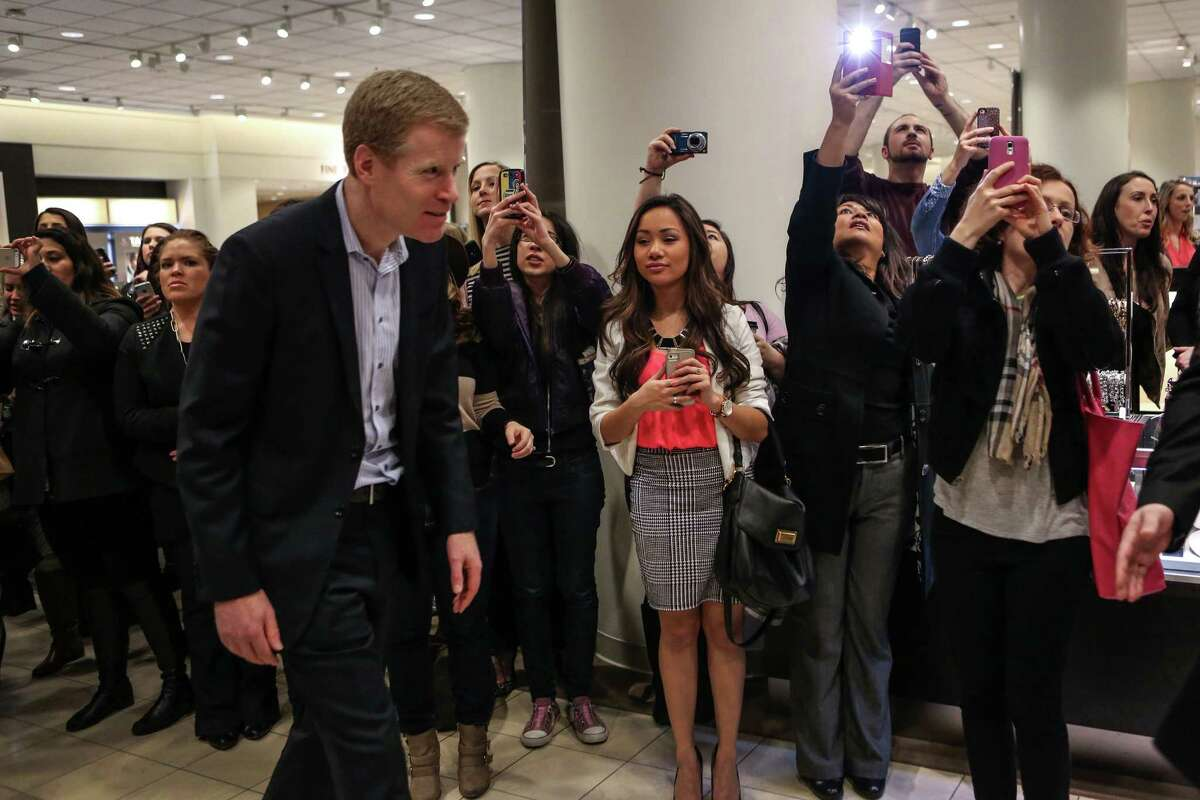Erik Nordstrom walks past people photographing actress Sarah Jessica Parker as Parker meets fans at the Seattle Nordstrom store.