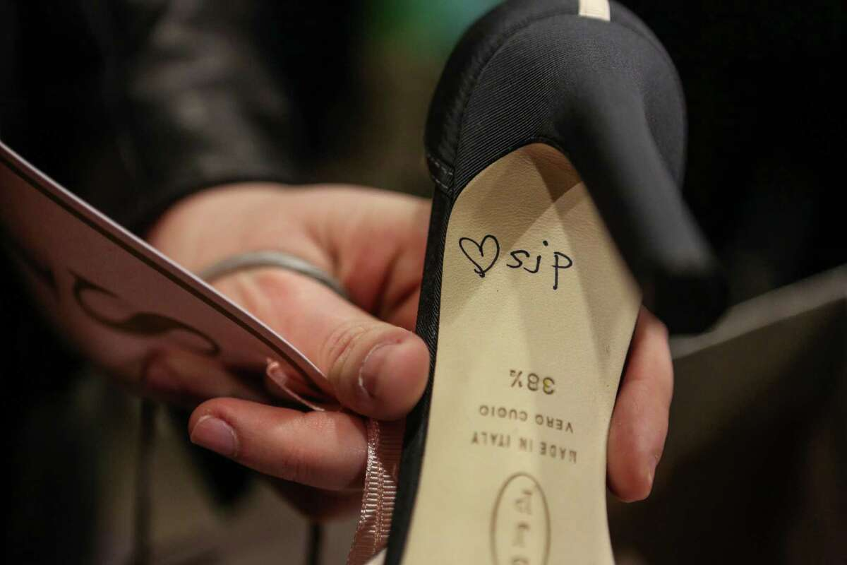 A fan shows a shoe autographed by actress Sarah Jessica Parker as Parker meets fans at the Seattle Nordstrom store.