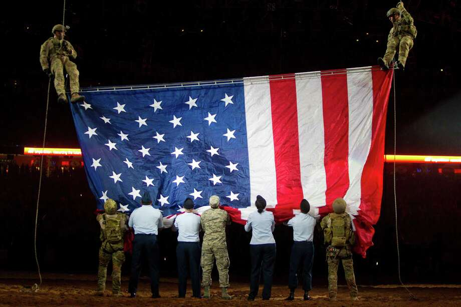 Members of the armed U.S forces receive the American flag during the Houston Livestock Show and Rodeo Armed Forces Appreciation Day, Wednesday, March 5, 2014, in Houston. Photo: Marie D. De Jesús, Houston Chronicle / © 2014 Houston Chronicle