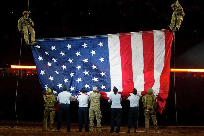 Members of the armed U.S forces receive the American flag during the Houston Livestock Show and Rode
