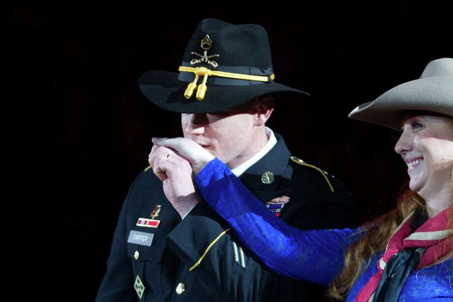 Medal of Honor recipient and soldier Ty M. Carter kisses the hand of his wife Shannon Carter as he is honored by the Houston Rodeo audience during the Armed Forces Appreciation Day, Wednesday, March 5, 2014, in Houston. Photo: Marie D. De Jesús, Houston Chronicle / © 2014 Houston Chronicle