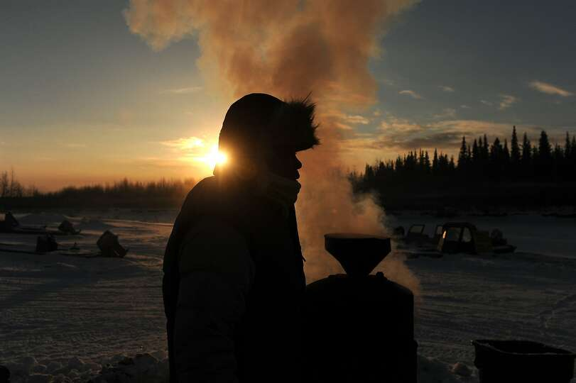 Iditarod musher Newton Marshall gets hot water from the wood fired heater at the Nikolai checkpoint