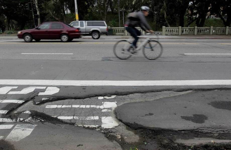 Kurt Wolfgang steers wide of a large pothole last year on Mission Street near San Jose Avenue in San Francisco. Photo: Paul Chinn / The Chronicle / ONLINE_YES
