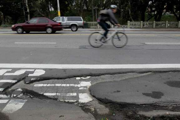 Kurt Wolfgang steers wide of a large pothole last year on Mission Street near San Jose Avenue in San Francisco.