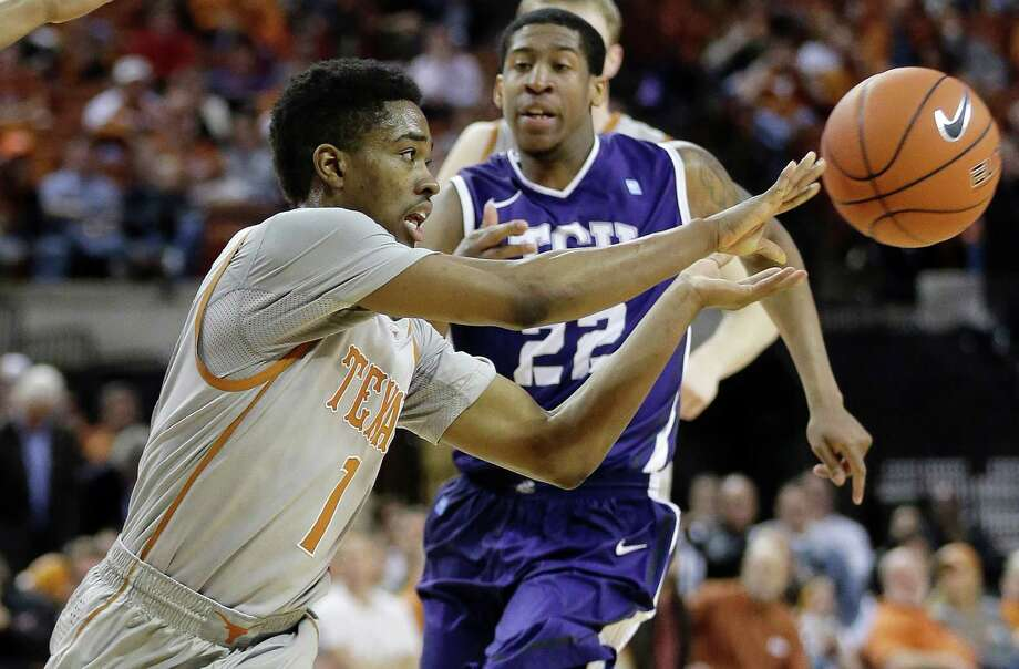 Texas' Isaiah Taylor (1) passes the ball as TCU's Jarvis Ray (22) closes in during the first half of an NCAA college basketball game, Wednesday, March 5, 2014, in Austin, Texas. (AP Photo/Eric Gay) Photo: Eric Gay, Associated Press / AP