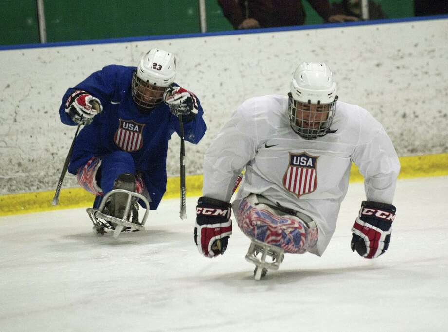 COLORADO SPRINGS, CO. FEBRUARY 26:  U.S. Paralympic Sled Hockey Team athletes, Nikko Landeros (R), and Rico Roman (L) chase after the puck during during practice on February 26, 2014 in Colorado Springs, Colorado. The team is practicing at the Sertich Ice Arena in Colorado Springs, Colorado for two days prior to their departure for Sochi, Russia to defend their 2010 Paralympic gold medal at the 2014 Paralympic Winter Games in Sochi, Russia. Photo: Jason Connolly, Getty Images / 2014 Getty Images