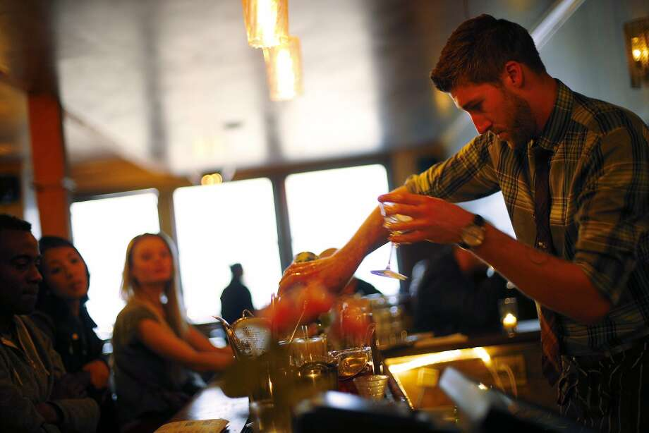 "Ian Anderson pours drinks at 15 Romolo. The ""glove law"" requires him to wear and change gloves when he adds garnishes. Photo: Carlos Avila Gonzalez, The Chronicle"