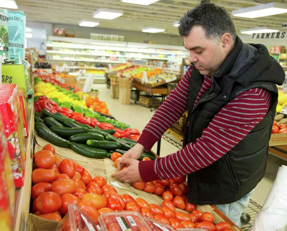 Yashar Cubukcu adds tomatoes to a display at Sophia Farmer's Market in the Springdale section of Stamford, Conn., on Tuesday, February 25, 2014. Photo: Lindsay Perry / Stamford Advocate