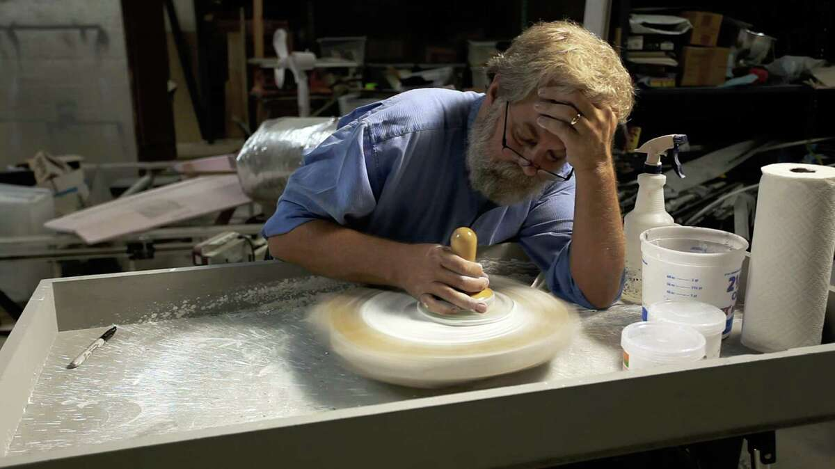 """This film image released by Sony Pictures Classics shows Tim Jenison polishing a lens in """"Tim's Vermeer."""" (AP Photo/Sony Pictures Classics)"""