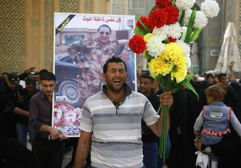 Ghaith Ismail, center, holds flowers during the funeral procession for his brother, Layth Ismail, in the Shiite holy city of Najaf, 100 miles (160 kilometers) south of Baghdad, Iraq, Thursday, March 6, 2014. Ismail, an Iraqi soldier, was killed during clashes with al-Qaida-led militants in Ramadi. (AP Photo/Jaber al-Helo) Photo: Jaber Al-Helo, Associated Press