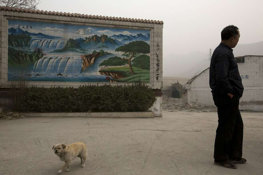 A gatekeeper of a demolished cement plant and his dog stand near the plant's gate on a severely polluted day in Shijiazhuang, in northern Hebei province. Photo: Alexander F. Yuan, Associated Press