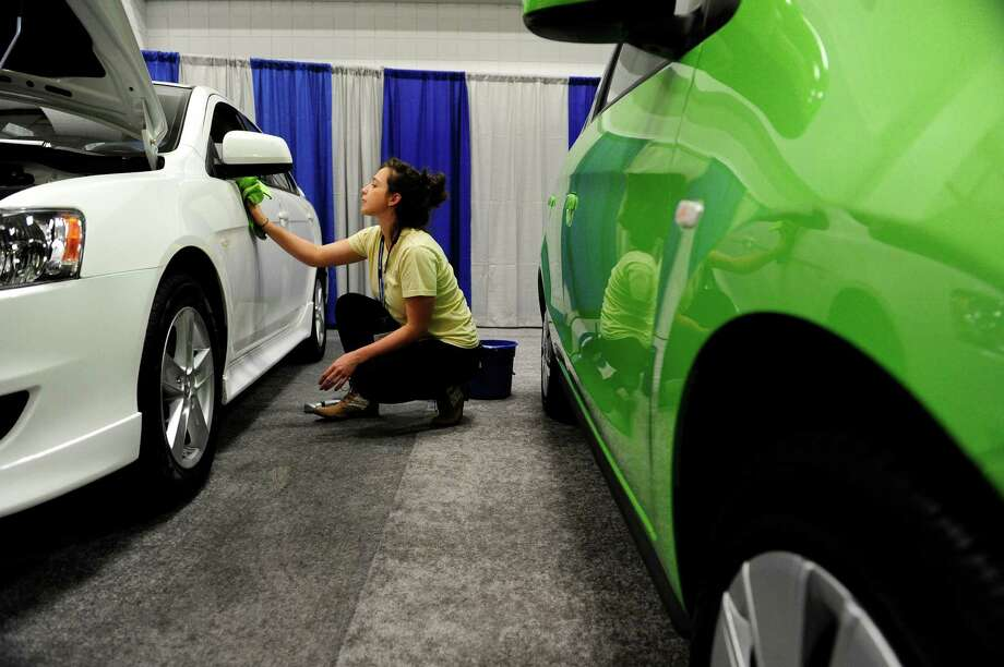 Car detailer Angel Giuliano shines up a car inside the Times Union Center as workers prepare the area for the auto show, which opens at 11 a.m. Friday.   (Paul Buckowski / Times Union) Photo: Paul Buckowski / 00026031A