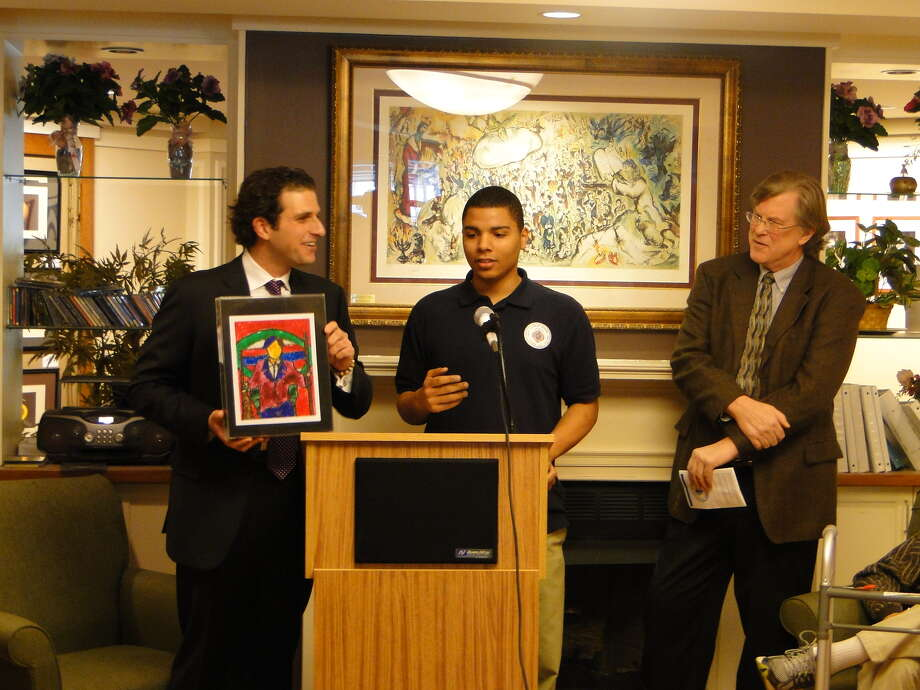 "LaSalle School student Titian, at podium, talks about his artwork, ""Revolutionary Suicide,"" a nod to Huey Newton's 1973 autobiography depicting African-American life. Art by LaSalle students is on display at Daughters of Sarah Senior Community in Albany. Flanking Titian are Daughters of Sarah board member Murray Massry, left, and LaSalle School Executive Director Bill Wolff.  The art will be on display through mid-March. (Courtesy LaSalle School)"