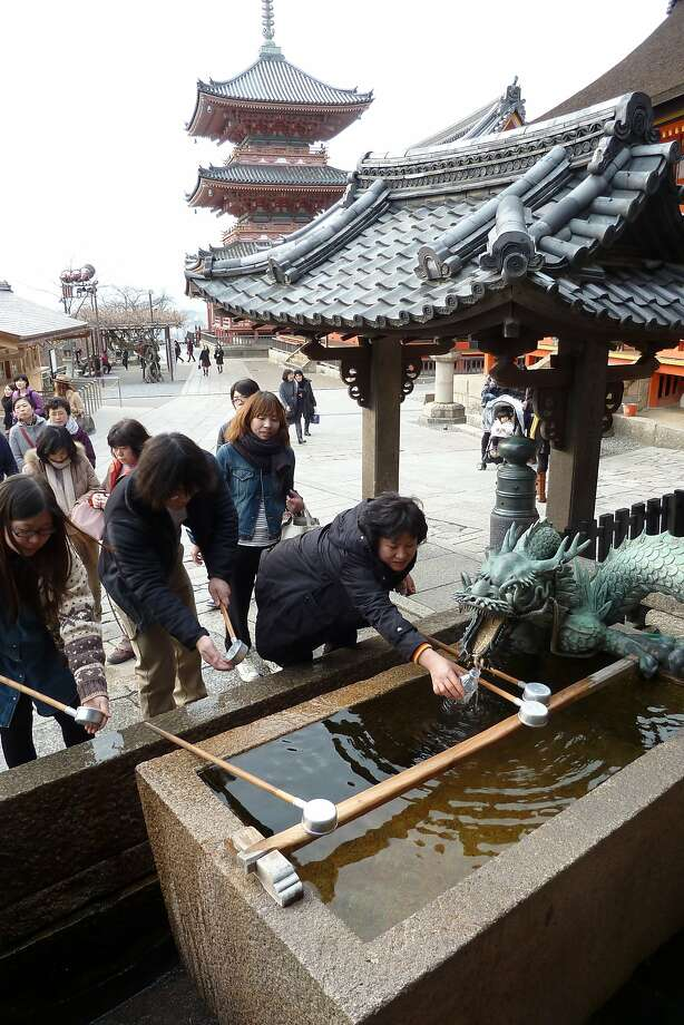 Visitors to the Kiyomizu-dera Buddhist temple in Kyoto sip sacred water from a spring fountain that is supposed to bring good fortune. Photo: Spud Hilton, The Chronicle