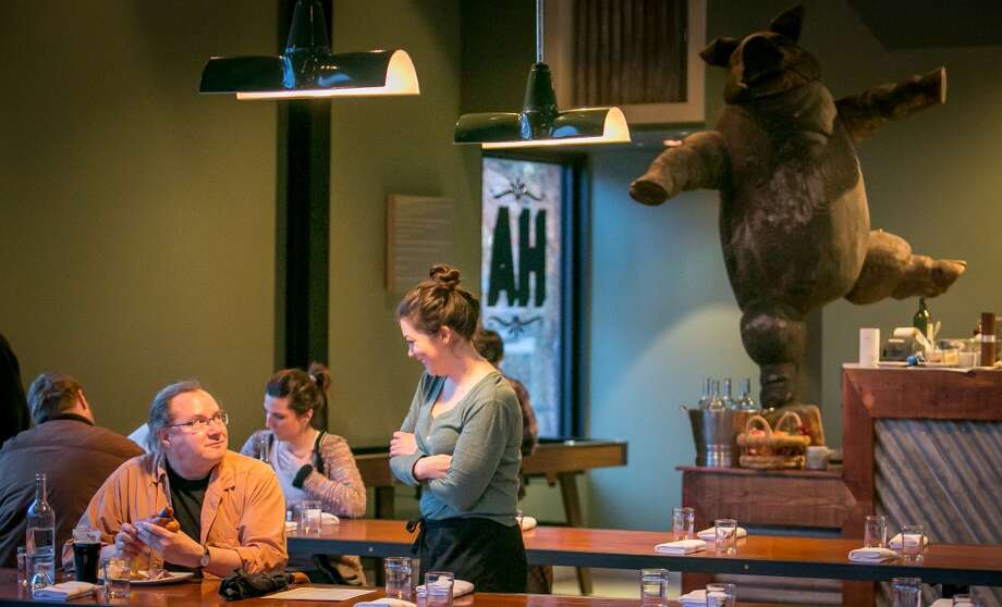 Diners enjoy dinner at Hog's Apothecary in Oakland. As does a dancing pig. Photo: John Storey, Special To The Chronicle