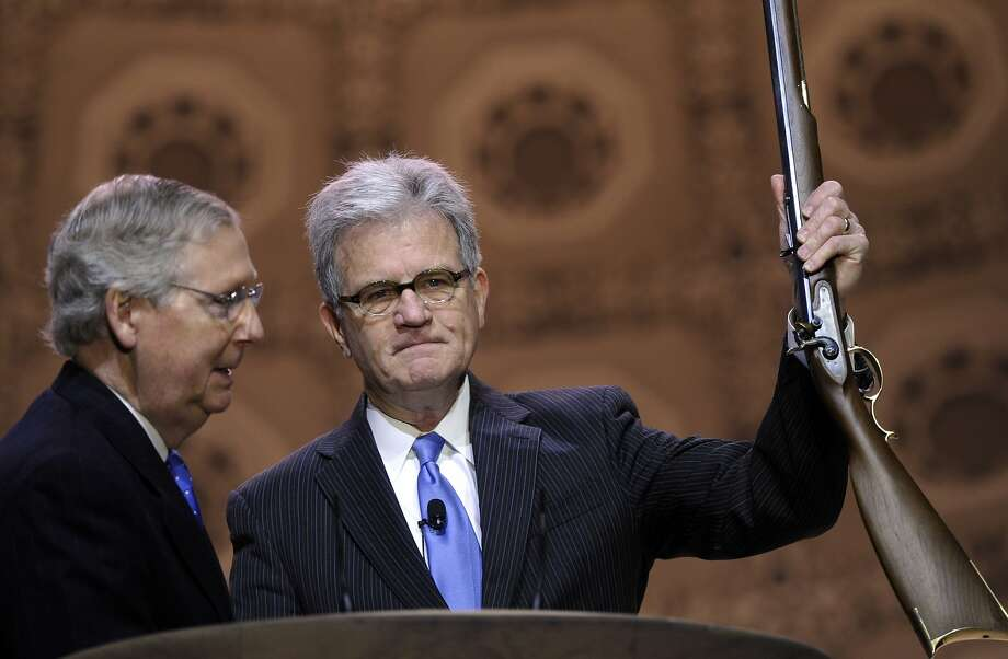 All you need now is a coonskin cap: Sen. Tom Coburn, R-Okla., holds a vintage rifle given him by Senate Minority Leader Mitch McConnell, R-Ky., on stage at the Conservative Political Action Committee annual conference in National Harbor, Md. The CPAC brings together prospective presidential candidates, conservative opinion leaders and Tea Party activists from coast to coast. Photo: Susan Walsh, Associated Press