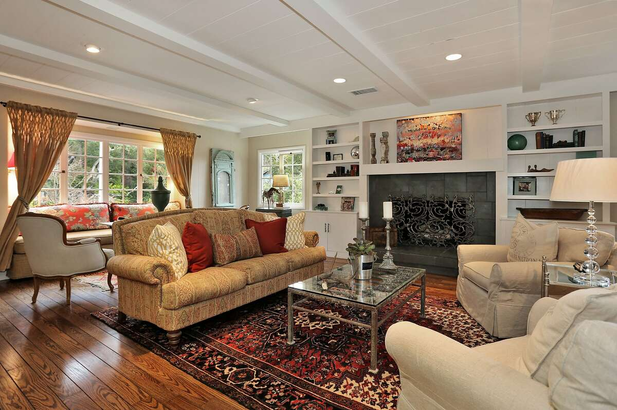The living room hosts a fireplace, built-in storage and divided light windows.
