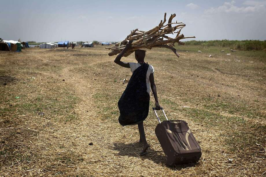 A woman laden with sticksto reinforce her shelter returns to an isolated makeshift IDP camp for ethnic Dinka refugees on a South Sudanese island. She is one of thousands who fled the fighting between the national army and rebel insurgents. Photo: JM Lopez, AFP/Getty Images