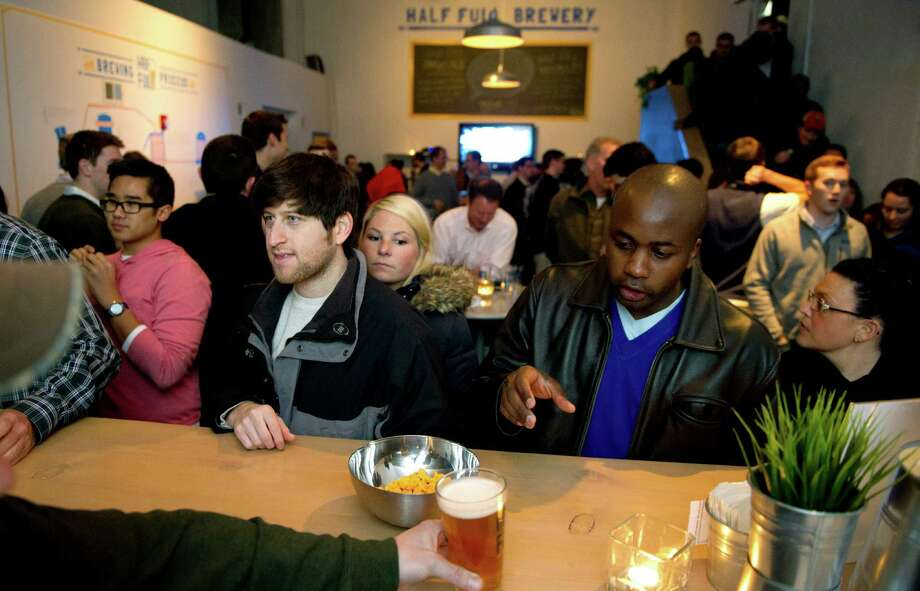 A crowd gathers for drinks and games at Half Full Brewery. The Stamford-based Brewery has signed a distribution agreement with ROGO Distributors of East Hartford. Photo: Lindsay Perry / Stamford Advocate