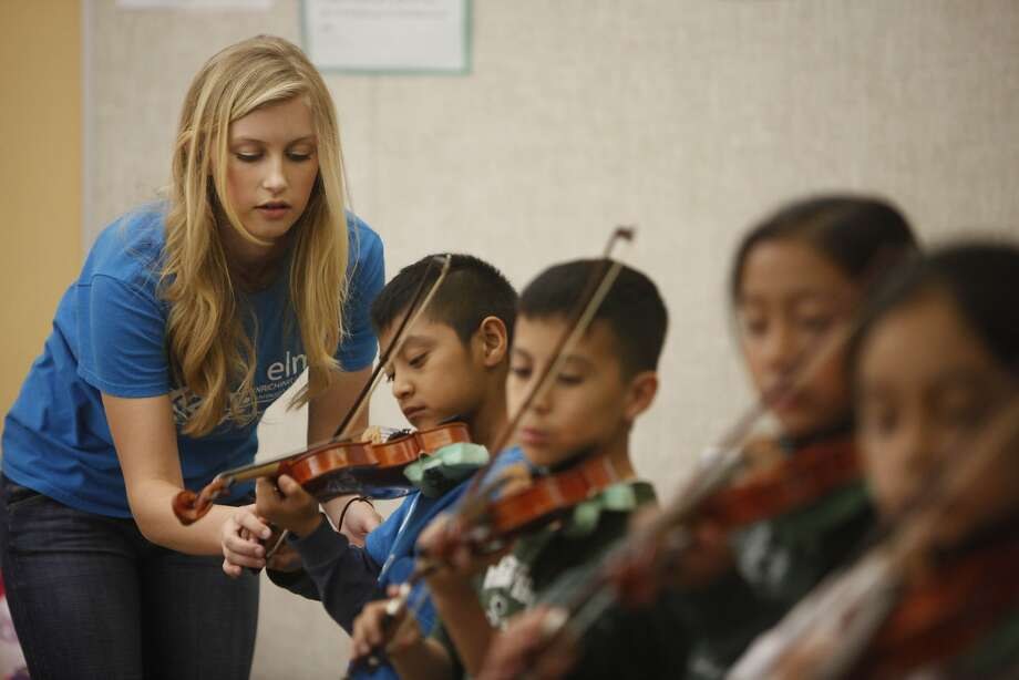Isabelle Gardner, 17, helps a student as she teaches violin to third-graders at Bahia Elementary School in San Rafael. Photo: Lea Suzuki, The Chronicle