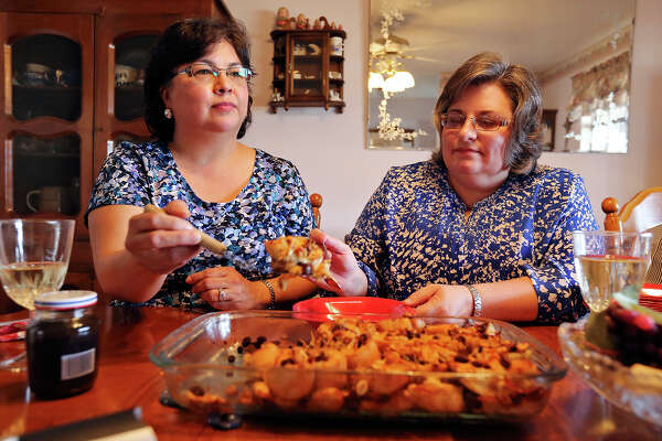 Alicia Aguirre (left), and Eileen Burell enjoy capirotada with friends during their monthly dinner club they call Wine Therapy  Sunday Feb. 16, 2014 at Laurie Marsh's (not pictured) home in Rio Medina, Tx.