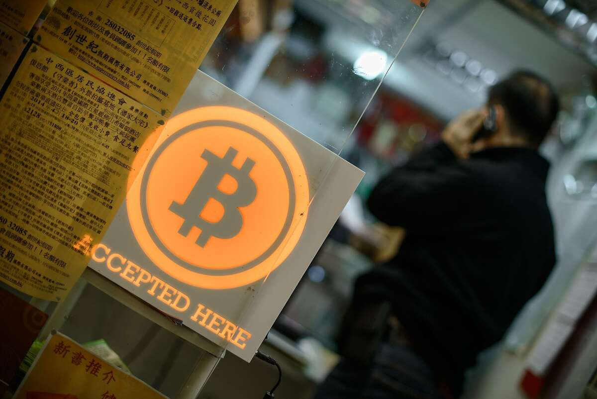 (FILES) A man talks on a mobile phone in a shop displaying a bitcoin sign during the opening ceremony of the first bitcoin retail shop in Hong Kong in this February 28, 2014, file photo. After years of speculation, the true identity of the mysterious person or group behind the Bitcoin revolution known as