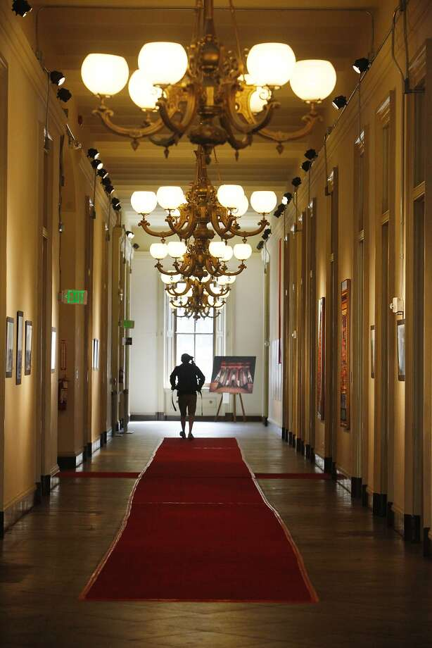 Above: A visitor walks through the main corridor at San Francisco's Old Mint, which may eventually become a museum.    Left: The Mint around 1874, when it opened. Photo: Lea Suzuki, The Chronicle