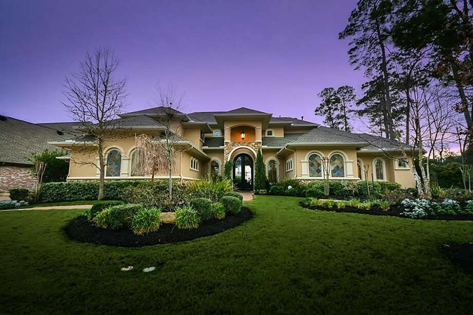 The stately custom home features beautifully-landscaped grounds.