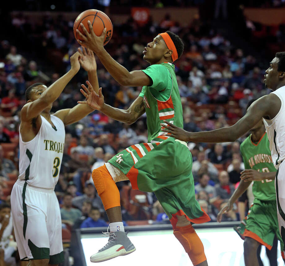 Jordon Harris splits a seam to the hoop past Johnathan Turner (right) and in front of Admon Gilder as  Sam Houston plays Dallas Madison at the Erwin Center in Austin in the state semifinals for 3A basketball on March 6, 2014. Photo: Tom Reel, San Antonio Express-News