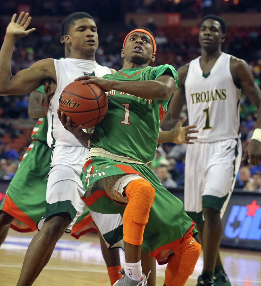 Jordon Harris leans back as he gets inside of Roderick Johnson (left) and Johnathan Turner as Sam Houston plays Dallas Madison at the Erwin Center in Austin in the state semifinals for 3A basketball on March 6, 2014. Photo: TOM REEL