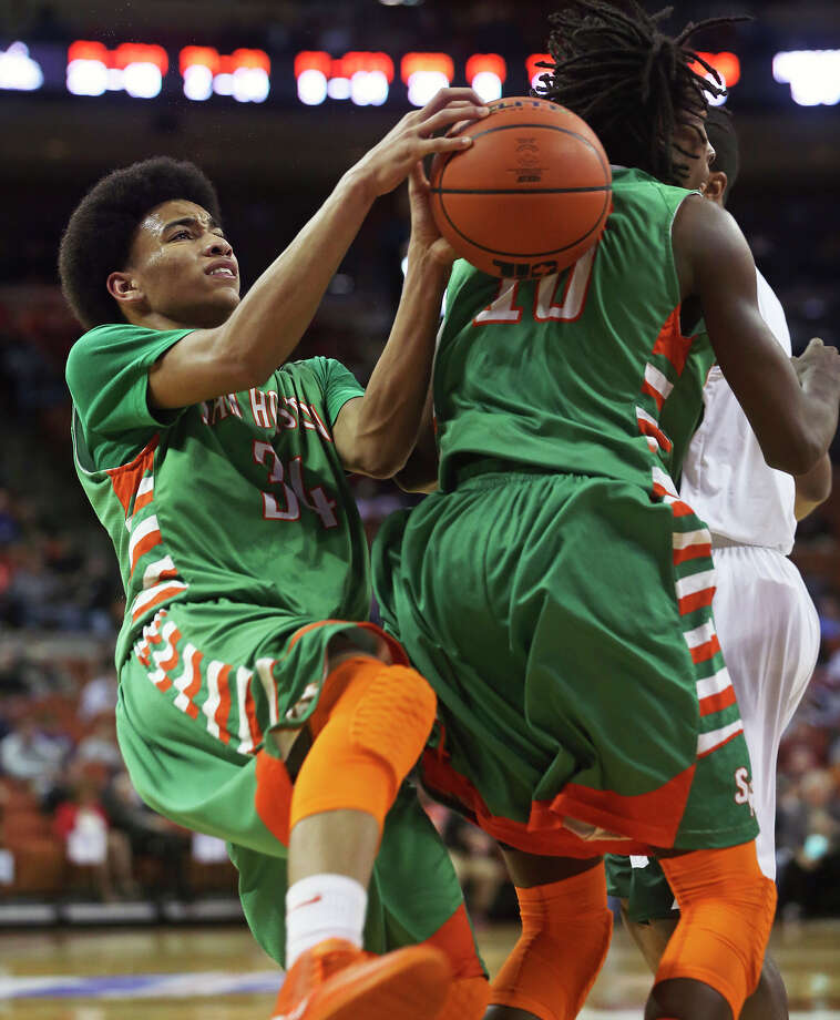 Robert Christian almost loses the ball on the back of teammate Raymonte Prime but recovers to make the shot as Sam Houston plays Dallas Madison at the Erwin Center in Austin in the state semifinals for 3A basketball on March 6, 2014. Photo: TOM REEL