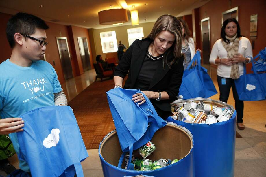 Salesforce.com employees Ernest Ng, left, helps Courtney Loomis dump her bag of canned food into a drum during a food drive at their Market St. offices in San Francisco, CA, Thursday, March 6, 2014. Photo: Michael Short, The Chronicle
