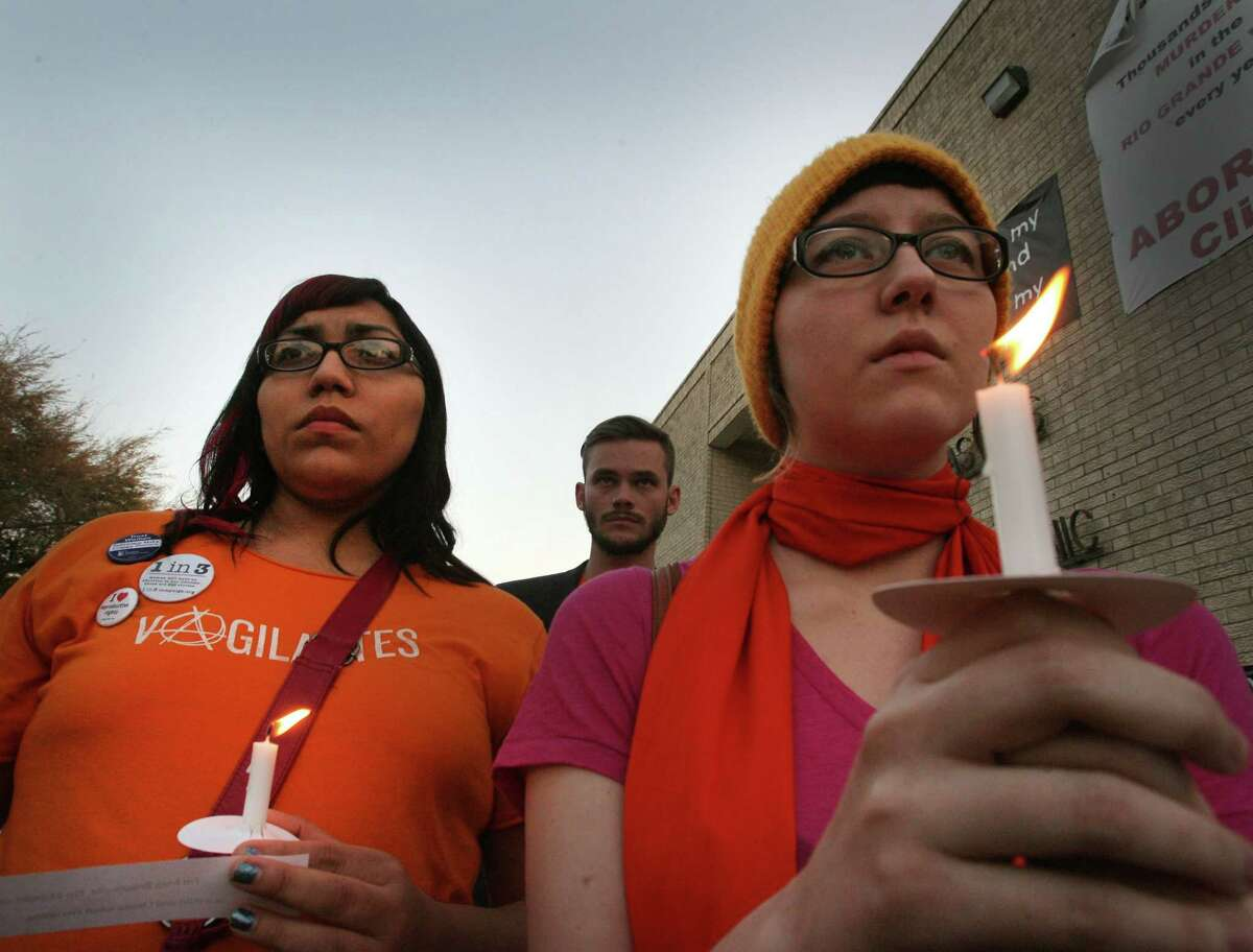 (L-R) Becca Arjona,26 Pharr and Melissa Eberlein,23,of McAllen listen as a story is told during a candle light vigil at the McAllen Women's Health Clinic Thursday March 6, 2014.(AP Photo/ Delcia Lopez The Monitor)