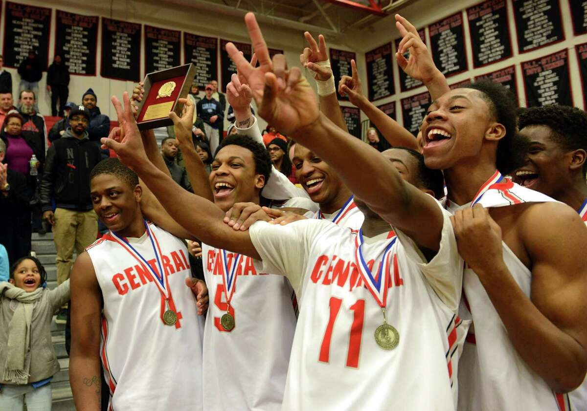 Central basketball players celebrate their FCIAC championship victory over Greenwich Thursday, Mar. 6, 2014, at Fairfield Warde High School in Fairfield, Conn.