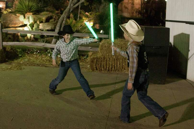 Seth Myers, 10, and his brother Noah, 7, have a light saber duel outside Reliant Stadium during the