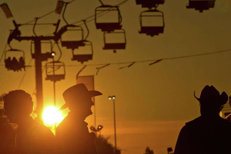The sun sets over the Rodeo Carnival during the third day of the Houston Livestock Show and Rodeo, T