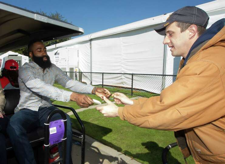 Houston Rockets guard James Harden gives rodeo volunteer Jeremy Johnson an autograph during the Hous