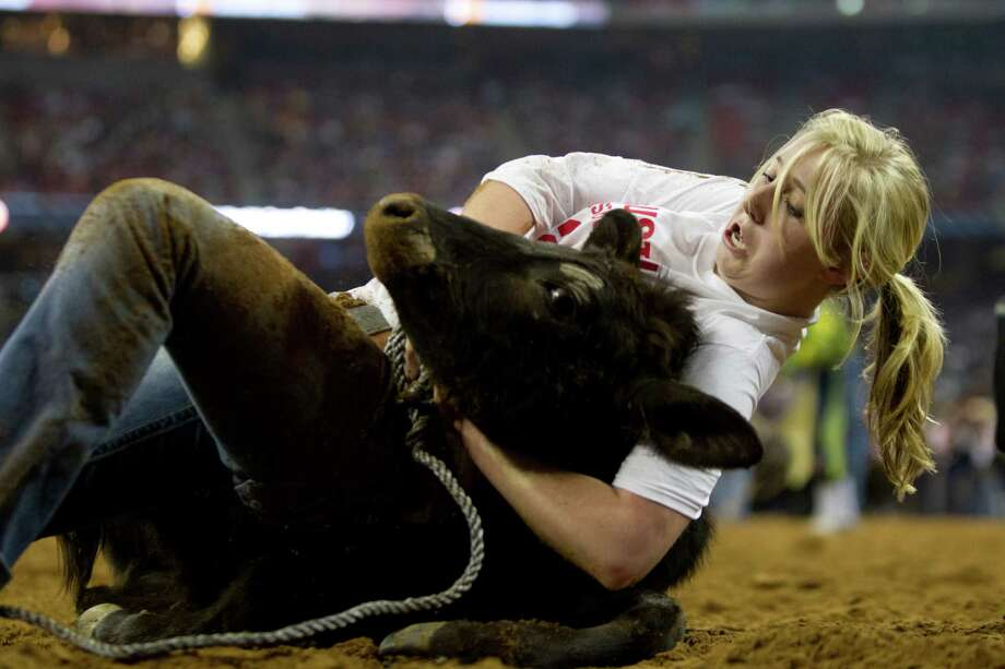Shelby Castilaw a Calf Scramble hangs on to her calf during Houston Livestock Show and Rodeo at Reliant Stadium on Thursday, March 6, 2014, in Houston. Photo: Marie D. De Jesús, Houston Chronicle / © 2014 Houston Chronicle