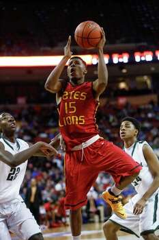 Houston Yates' Brandon Hayes (15) goes up for a shot after driving past Kennedale's VJ Hughes (22) and Brandon Conwright (24) during a boys' UIL Class 3A state basketball semifinal, Thursday, March 6, 2014, in Austin, Texas. Yates defeated Kennedale 86-79. (AP Photo/Tamir Kalifa) Photo: Tamir Kalifa, Associated Press / FR170773 AP