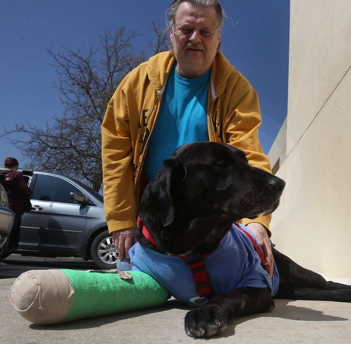 Ronald Zawacki-Maldonado pets Debbie outside South Texas Veterinary Specialists in San Antonio. The formerly stray dog then headed home to Zawacki-Maldonado's place in Eagle Pass, where she was hit by a car and injured in January.