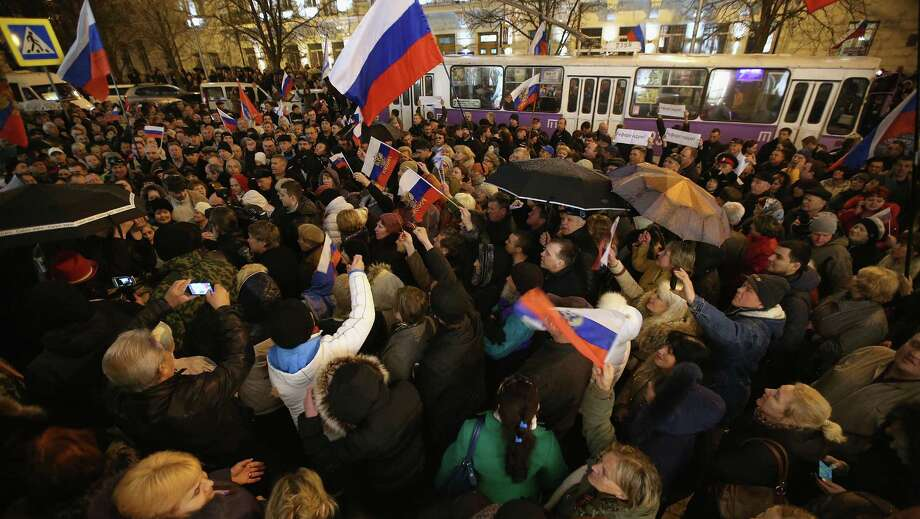 People waving Russian flags gather in Sevastopol, Ukraine, to hear the announcement confirming that the Sevastopol regional council supported the vote for Crimea to secede from Ukraine and join Russia passed by the Crimean Parliament. Photo: Sean Gallup / Getty Images / 2014 Getty Images