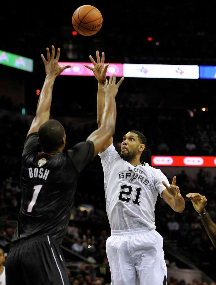 San Antonio Spurs forward Tim Duncan, right, shoots against Miami Heat forward Chris Bosh during the first half of an NBA basketball game on Thursday, March 6, 2014, in San Antonio. (AP Photo/Darren Abate) ORG XMIT: TXDA101 Photo: Darren Abate / FR115 AP