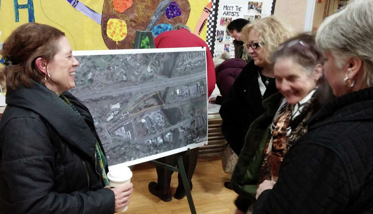 Plans for a 96-unit apartment building on Bronson Road as inspected by some of the people who turned out for an Inland Wetlands Commission hearing on the project. All of the speakers at the meeting opposed the plan.