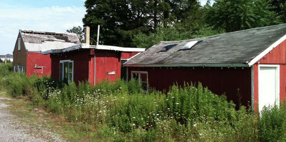 This July 2013 photo shows a derelict, one-time garden center on the Southport stretch of the Post Road, where a new building will be constructed to house the gourmet food market, Garelick & Herbs, now in Westport. Photo: File Photo / Fairfield Citizen