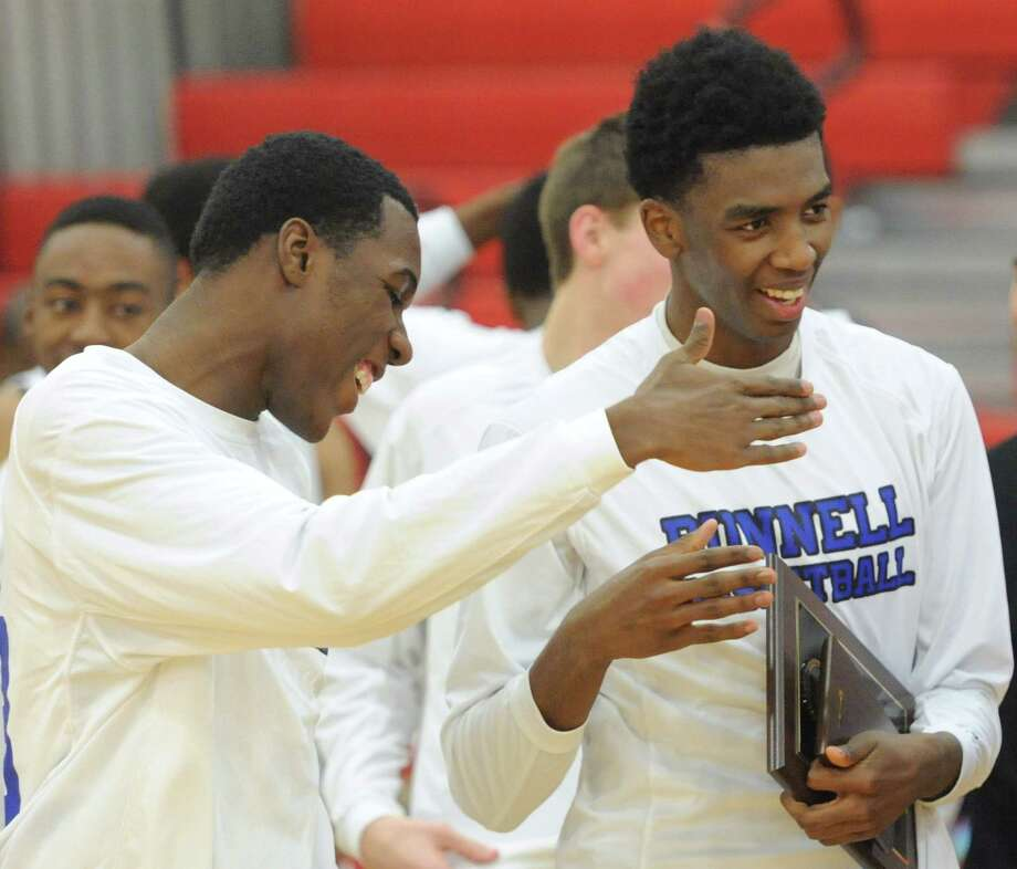 Issac Vann, right, holds the SWC champion trophy while celebrating with teammate Romkiyns Joseph after Bunnell's 68-64 win over Kolbe Cathedral in the SWC boys basketball championship game at Pomperaug High School in Southbury, Conn. Thursday, March 6, 2014. Photo: Tyler Sizemore / The News-Times