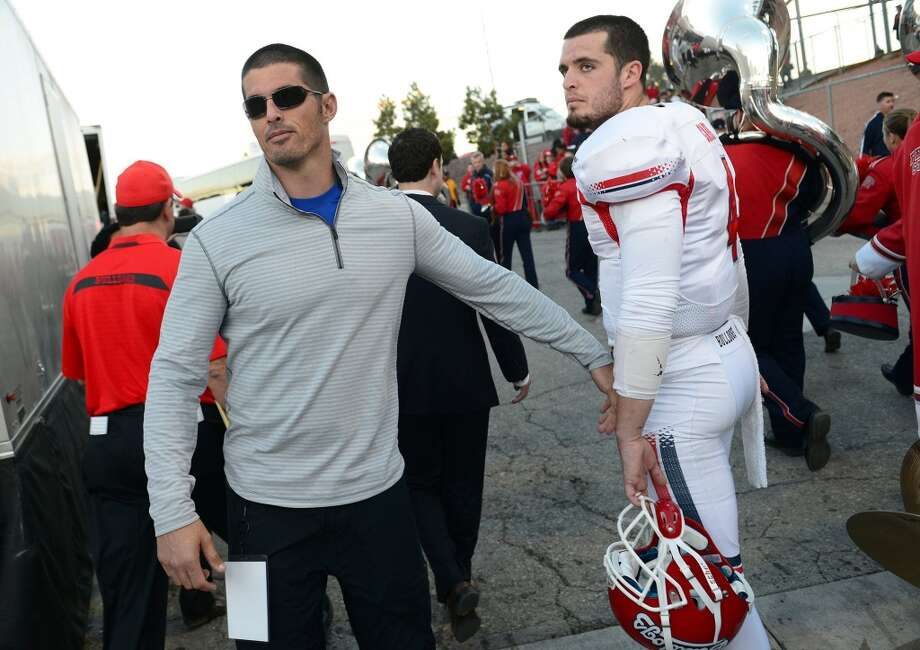 David Carr, left, has a brief word with his brother, Derek Carr, after USC defeated Fresno State in the Las Vegas Bowl on Dec. 21, 2013. David Carr did not play in the NFL in 2013. Photo: Craig Kohlruss, MCT